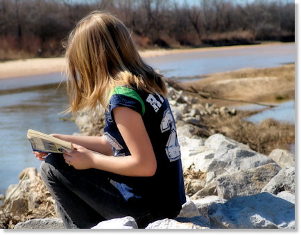Haley reading at the river.