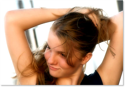 Young Girl with hands up in a hair tying motion